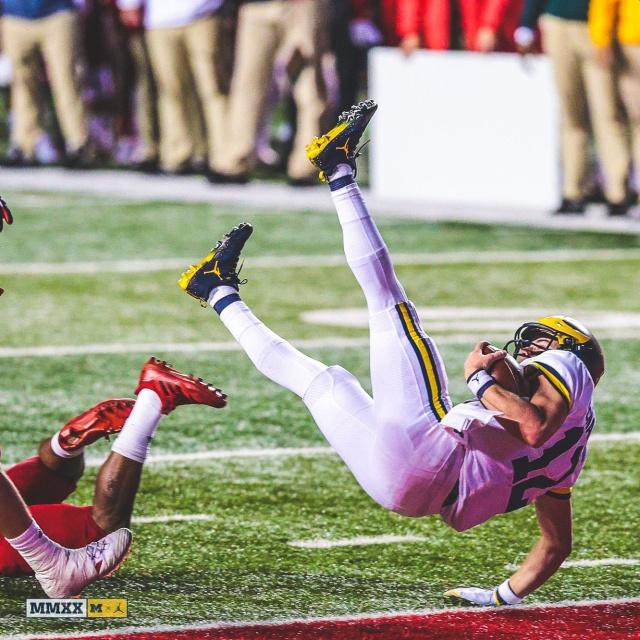 Michigan Quarterback Cade McNamara (12) Evades a Rutgers Defender for a Touchdown.